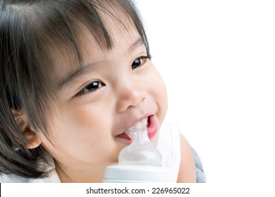 Closeup portrait of happy Asian little girl with bottle of milk ,on white background