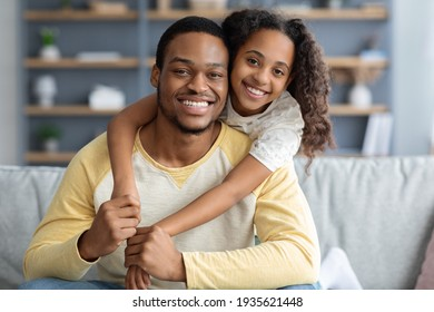 Closeup portrait of happy black father and daughter embracing