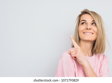 Closeup portrait of happy blonde hair female wears pink sweater indicates with fore finger aside, looking up, demonstrates something at blank copy space for advertisement. People and emotion concept