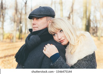 Closeup portrait of a happy blonde mature woman and beautiful middle-aged brunette, looking away. Pensive, dreamy loving couple of 45-50 years old walks in the autumn park in warm clothes, in a coat