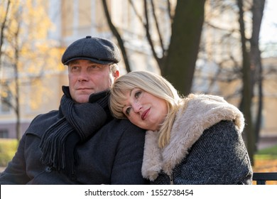 Closeup portrait of happy blonde mature woman and beautiful middle-aged brunette, looking away. Loving couple of 45-50 years old walks in the autumn park in warm clothes, in coat and enjoys life