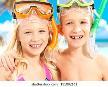 Closeup portrait of the happy brother with sister enjoying at beach.  Laughing children standing together in swimwear with swimming mask on head .