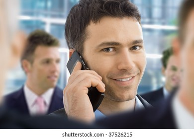 Closeup portrait of happy businessman talking on mobile in crowd in office lobby.