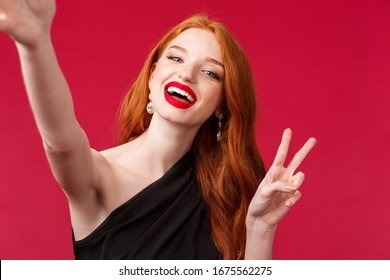 Close-up portrait of happy charming redhead woman enjoying party, taking selfie with peace sign and beaming smile, wear black evening dress and red lipstick, stand red background