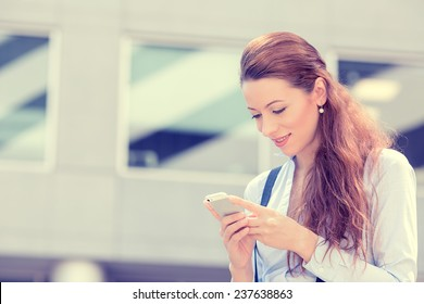 Closeup portrait, happy, cheerful, girl, excited by what she sees on cell phone, isolated background corporate office. Facial expression, reaction. Business woman sending text message from her mobile