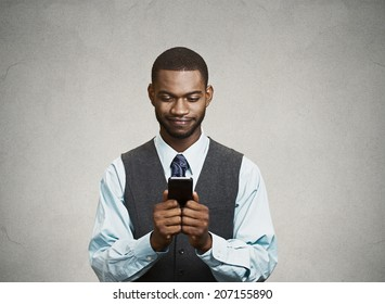 Closeup portrait happy cheerful, young adult business man, excited by what he sees on his cell phone isolated black background. Positive human emotion facial expression, feeling reaction body language