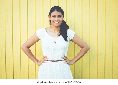 Closeup portrait, happy confident successful pretty young woman in white dress with hands on hips, isolated on yellow background . Positive human emotions, facial expressions