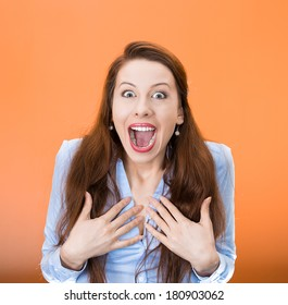 Closeup portrait of happy cute young beautiful woman looking excited, surprised in full disbelief, hands on chest, it's me? isolated orange, red background. Positive human emotions,facial expressions