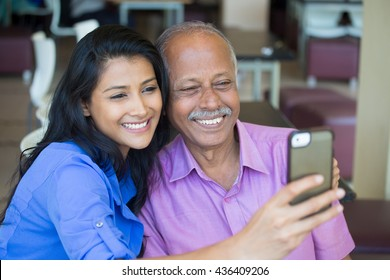 Closeup portrait happy elderly gentleman in pink shirt and lady in blue top taking selfie together, isolated indoors background. Say cheese and smile