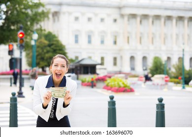 Closeup portrait of happy, excited corrupt politician in washington dc, holding dollar bills isolated on Capitol building background. Human emotions and facial expressions. Greed, politics concept