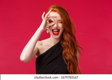 Close-up portrait of happy and excited good-looking redhead girl telling to grab your chance, show peace sign on eye and look through fingers as if seeing something on distance, smile pleased