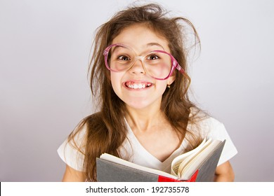 Closeup portrait happy, excited, smiling, funny looking little girl with glasses, holding book, discovered something new, isolated grey blackboard. Human facial expression, emotion, feeling, reaction