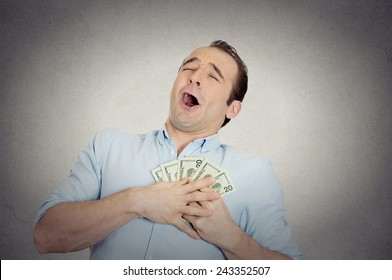 Closeup portrait happy excited successful business man in love with money, funny looking guy holding dollar bills in hand isolated grey wall background. Human emotions, facial expressions, feeling