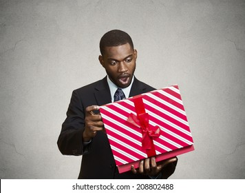 Closeup portrait happy excited surprised young businessman about to open unwrap red gift box isolated grey background, enjoying his present. Positive human emotions, facial expression feeling attitude