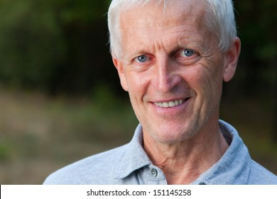 Closeup portrait of happy face of grey-haired old man. Outdoor. In the park. Blue jeans. Grey t-shirt.