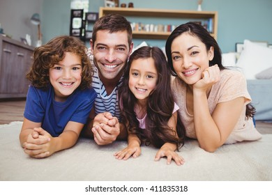 Close-up portrait of happy family lying on carpet at home