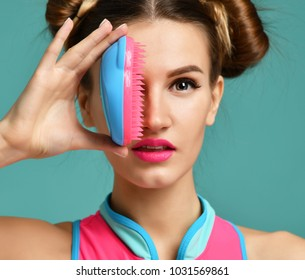 Closeup portrait of happy fashion brunette woman close eye with colorful pink blue popular hair comb brush on modern mint background