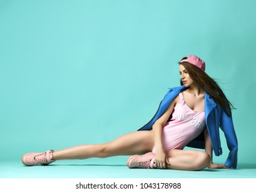Closeup portrait of happy fashion brunette woman lying top view in pink glamour body vest on modern mint background
