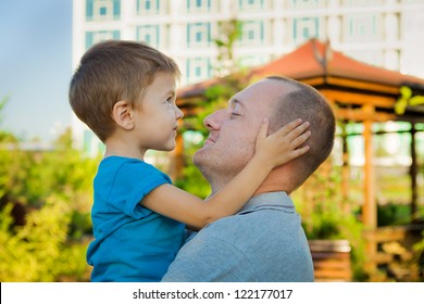 Closeup portrait of a happy father and son playing outdoors and having fun