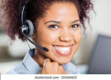 Closeup portrait of happy female customer service representative wearing headset in office