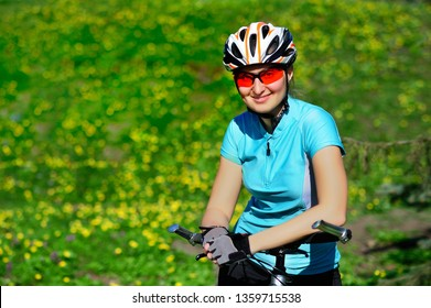 Closeup portrait of a happy female cyclist at the green lawn background