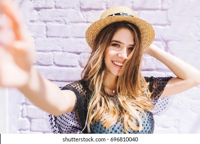 Close-up portrait of happy girl with mid-back length hair making selfie and holding straw hat. Outdoor photo of laughing romantic woman taking picture of herself in summer morning.