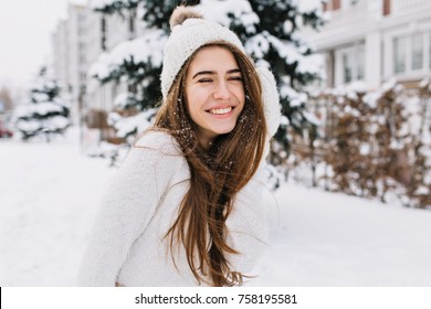 Close-up portrait of happy girl in woolen sweater enjoying winter moments. Outdoor photo of long-haired laughing lady in knitted hat having fun in snowy morning on blur nature background.