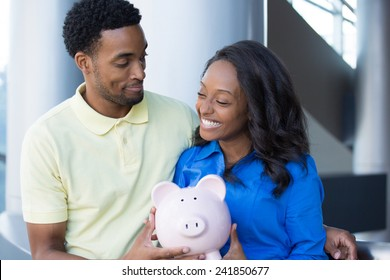 Closeup portrait, happy handsome couple or two business people holding pink piggy bank looking at each other, laughing.  Smart financial decisions