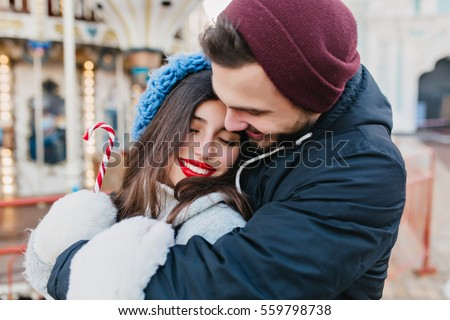 Closeup portrait happy lovely couple chilling outdoor on street. Romantic moments,taking care, real love, true emotions, girl with red lips holding a candy.