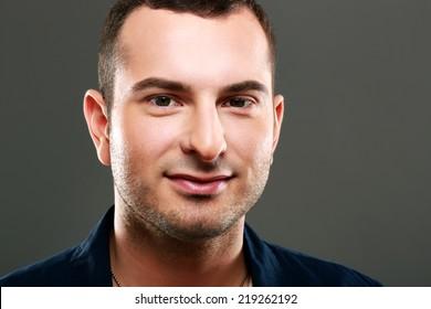 Closeup portrait of happy man on gray background
