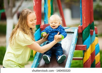 Closeup portrait of a happy mother and son playing on playground and having fun. Summer park. Outdoors.