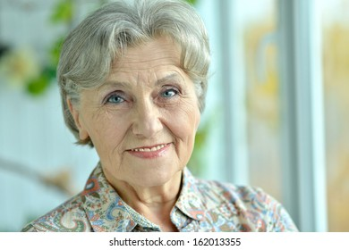 Close-up portrait of a happy older woman at home