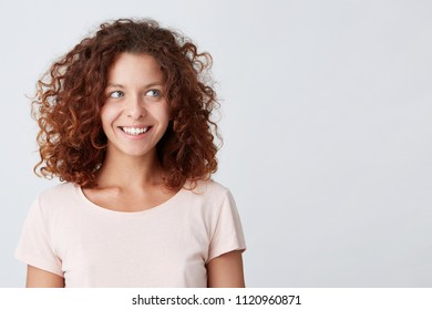 Close-up portrait of Happy pretty curly young woman smiles and looks aside, Isolated  over white background with copy space