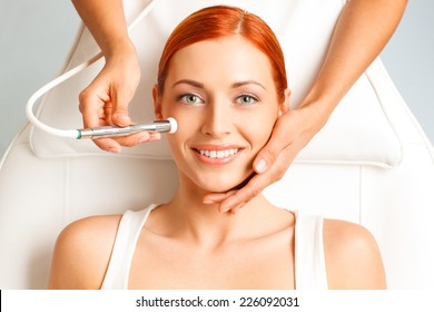 closeup portrait of happy redheaded woman getting microdermabrasion procedure in a beauty salon