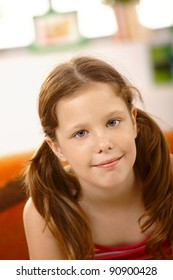 Closeup portrait of happy schoolgirl smiling at camera?