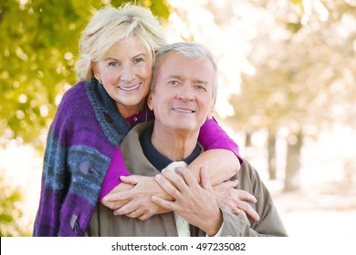 Close-up portrait of happy senior couple  smiling to the camera while relaxing at outdoor and elderly woman hugging old man.