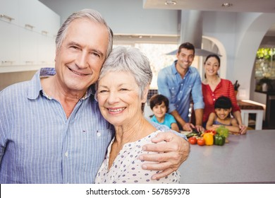 Close-up portrait of happy senior couple with family preparing food in background
