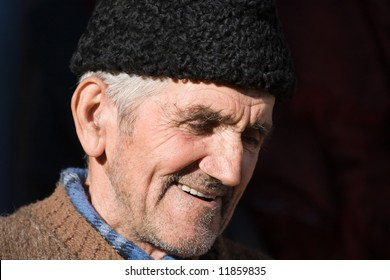 Close-up portrait of a happy senior farmer with black cap