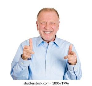 Closeup portrait of happy senior mature man with two hands guns sign gesture pointing at you camera, isolated on white background. Positive human emotion facial expression feelings, signs and symbols