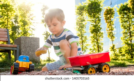 Closeup portrait of happy smiling 3 years old child boy digging sand on playground with toy plastic truck or excavator. Child palying and having fun at park at summer