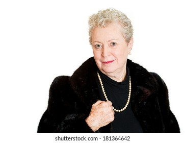 Closeup portrait of happy smiling amiable mirthful successful pretty senior mature woman in black fur with holding necklace, isolated on white background. Positive emotion facial expression feelings.