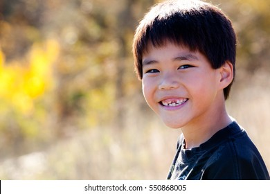 Closeup portrait of a happy, smiling Asian boy missing a front tooth