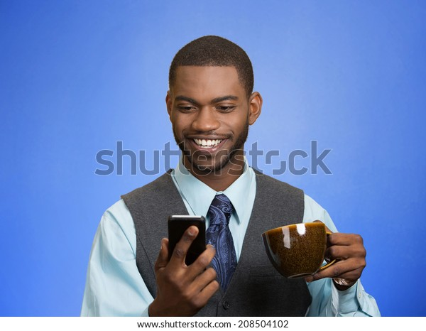 Closeup portrait happy, smiling business man reading good news on smart phone, lawyer holding mobile, drinking cup coffee isolated blue background. Human face expression, emotion, corporate executive