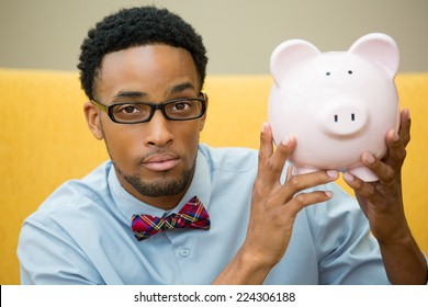 Closeup portrait happy, smiling businessman in black glasses and bowtie, holding pink piggy bank, isolated indoors office background. Financial budget savings, smart investment concept