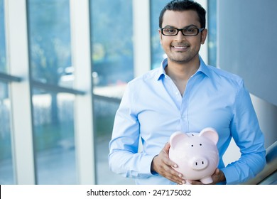 Closeup portrait happy, smiling businessman with black glasses, holding pink piggy bank, isolated indoors office background. Financial budget savings, smart investment concept