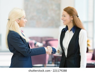 Closeup portrait happy smiling businesspeople, attractive business women shaking hands, standing in a hallway of corporate office. Positive human face expressions, emotions, attitude