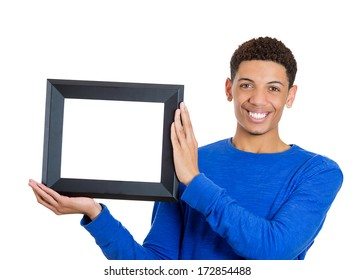 Closeup portrait of happy smiling confident handsome man holding a rectangular square empty blank picture frame - Copy space provided. Positive emotion facial expression feelings
