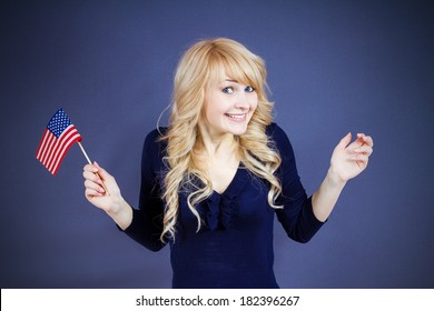 Closeup portrait happy, smiling excited blonde woman, employee, worker, student holding united states of america flag, USA, isolated dark blue background. Positive emotions, face expressions, attitude