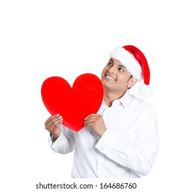 Closeup portrait of happy smiling handsome man in red santa claus hat looking upwards and holding large  heart to chest daydreaming ,isolated on white background, space to left. Positive emotion