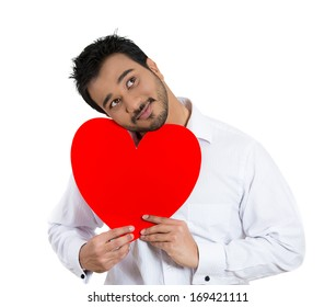 Closeup portrait of happy smiling handsome man looking upwards, holding large red heart to chest daydreaming of women in love ,isolated on white background. Positive emotion facial expression feelings